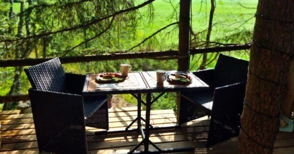 Palapinė medyje. Staliukas su kėdėmis dviems terasoje